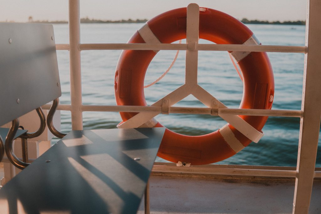 Photo of a bench on a boat in the water with an orange round life saver on the outside.