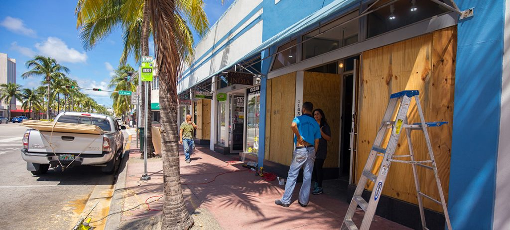 Photo of a couple talking in front of a boarded up business with palm trees and a parked truck on the road.