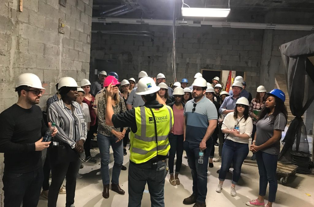 Photo of a persons wearing yellow safety vest speaking to a group of people wearing hardhats.
