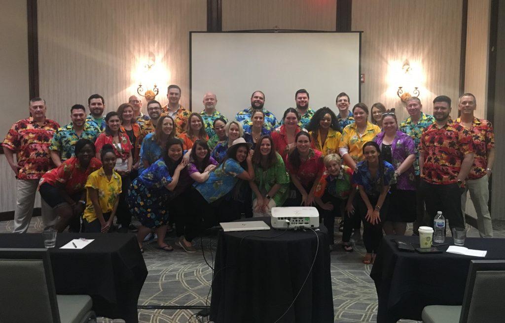 Group photo of a team wearing Hawaiian shirts.