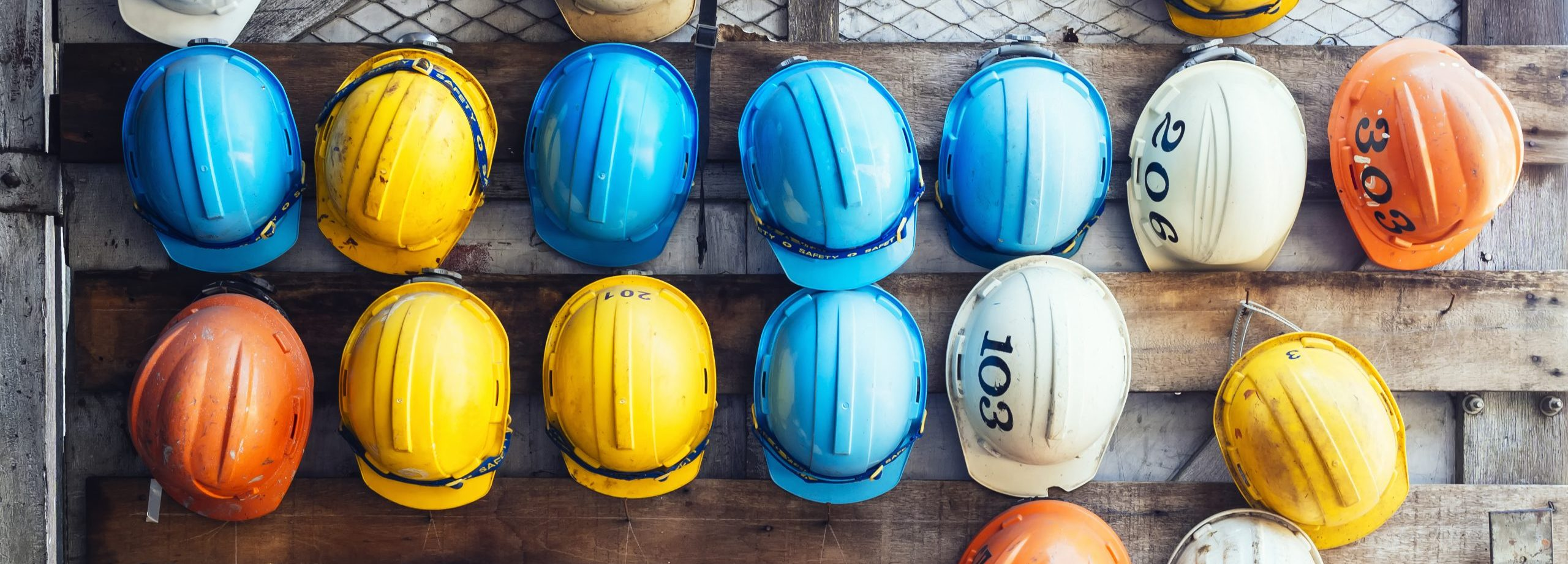 Photo of blue, yellow, orange and white hardhats hanging on a wooden wall.