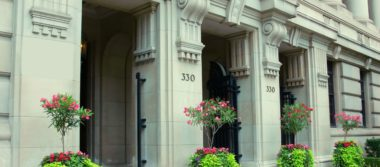 Photo of a large building with intricate architecture and decorative plants sitting in between entryways.