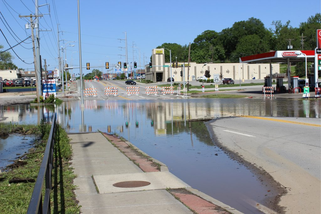 Photo of a flooded street with businesses in the background.